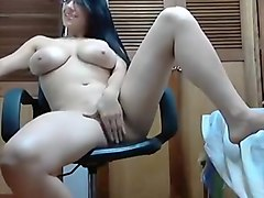 Busty brunette on chair in front of webcam fingering her horny pussy and teasing